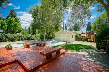 Newer deck overlooking the pool-size backyard with brand new rebuilt garage with electrical and original sliding doors, in addition to a swing, grassy area, and potential RV parking. One of the largest yards in the neighborhood.