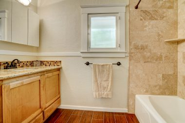 Remodeled bathroom with granite counter and tiled shower enclosure.