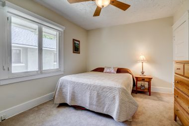 Middle bedroom with newer carpeting, ceiling fan, and lovely window welcoming lots of natural light.