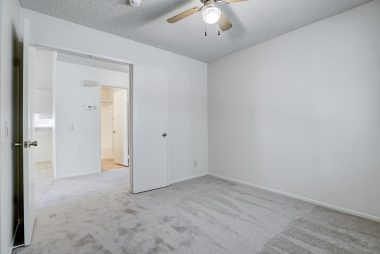 Front bedroom with double door entry, brand new carpet, and ceiling fan.