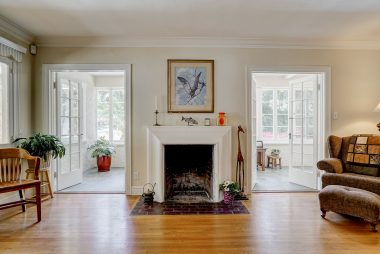 Wood-burning fireplace flanked by charming French doors which lead to the side porch with beamed ceiling and tile flooring.