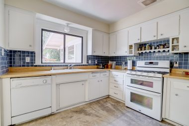 Vintage kitchen with dishwasher and gas stove, as well as lots of cabinetry and a walk-in pantry.
