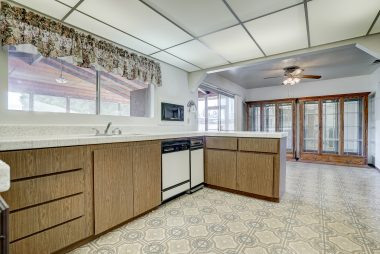 Vintage kitchen with dishwasher, trash compactor, gas stove, microwave, and refrigerator.