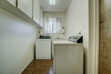 Indoor laundry room with plenty of overhead cabinetry.