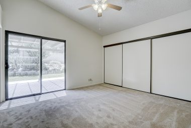 Large master bedroom suite with cathedral ceiling, huge closet space, ceiling fan, brand new carpeting, and rehabbed sliding glass doors overlooking spacious side patio.