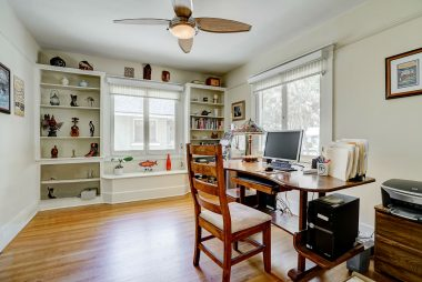 A set of lovely French doors welcomes you into the front room, currently used as an office, with built-in book shelves, ceiling fan, and hardwood floors, which overlooks the front yard.