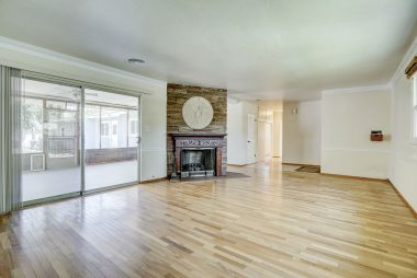 Spacious living room with hardwood floors, fireplace, and slider into the bonus screened-in room overlooking the back yard.