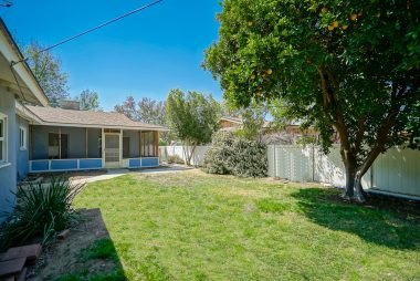 Pool-size back yard with orange and avocado trees, white vinyl fence, and view of screened-in bonus room.