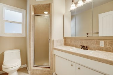 Vintage 3/4 bathroom with newer toilet and light fixture.