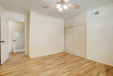 Bedroom #3 with hardwood floors, ceiling fan, and large closet.