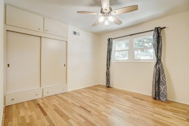 Bedroom #2 with hardwood floors, ceiling fan, and large closet.