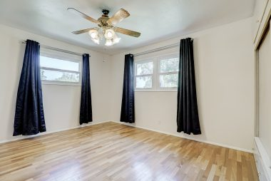 Bedroom #1 with hardwood floors, ceiling fan, and large closet.