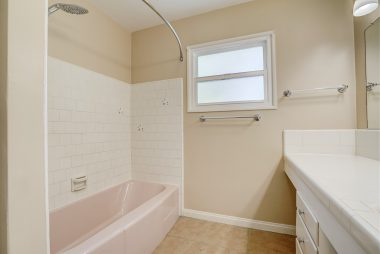 Spacious hallway bathroom with tile flooring and plenty of counter space.