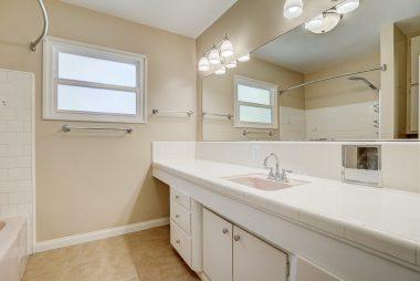 Vintage hallway bathroom with tile flooring and soaking tub (see next photo).