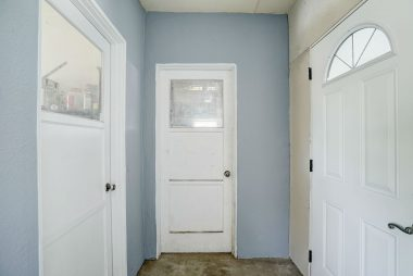 Enclosed step-down breezeway with large storage room to the left, garage straight ahead, and exit door to side yard facing Brentwood Avenue.