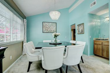 Spacious formal dining room with wet bar and vaulted ceiling.