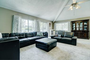 Living room with vaulted ceiling and sliders to front balcony.