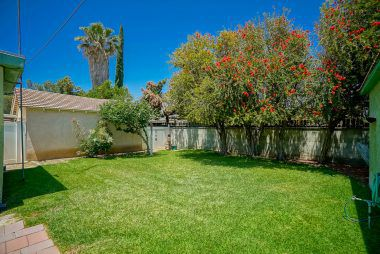 Lovely backyard with privacy block wall and mature landscaping.
