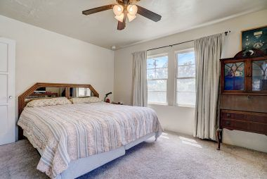Large bedroom with carpeting over hardwood floors, large closet, and ceiling fan.