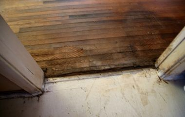 Appears to be water damage to wood floors at entry to kitchen from dining area/living room.