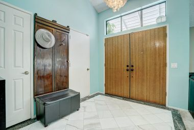 Formal entry with chandelier and marble flooring with doorways to coat closet and garage.