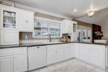 Remodeled kitchen with granite counters, tile floor, dishwasher, glass fronted cabinets, and breakfast bar....all overlooking the family room.