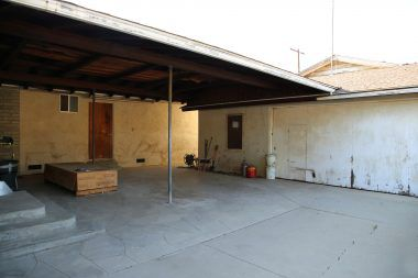 View of covered patio area between house and detached 2-car garage plus workshop/storage room (which was permitted in 1957).