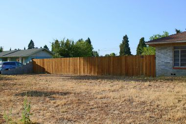 View of fenced vacant lot next door which is also for sale.