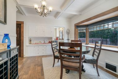 Formal dining room with bay window, coffered ceiling, and built-in hutch.