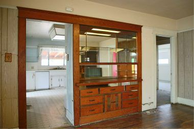 Original built-in hutch in formal dining room with view into the kitchen on the left and hallway to bedrooms on the right.