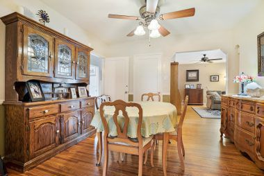Formal dining room with hardwood floors and ceiling fan, with view into the living room.