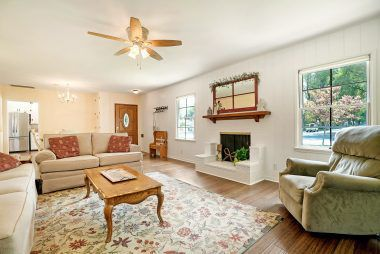 Spacious living room with gas and wood-burning fireplace, bamboo floors, and ceiling fan.