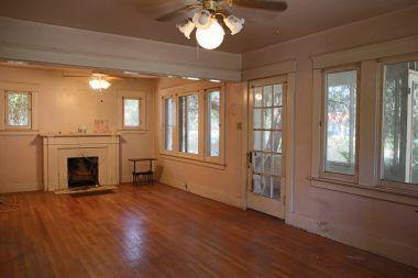 Living room with original hardwood floors, original window frames, and fireplace.