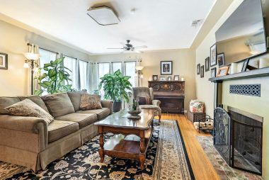 Gorgeous and elegant living room with hardwood floors, fireplace and ceiling fans.