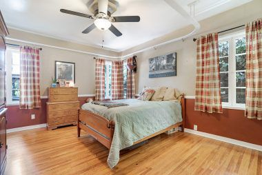 Huge bedroom facing the back of the house, with ceiling fan, hardwood floors, and a train track suspended from the ceiling for train buffs.