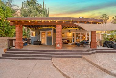 Twilight view of the back covered patio which is ideal for year-round entertaining. Note the custom-stamped concrete surrounding the pool area.