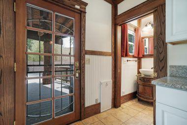 Same view of bathroom with branded pocket door open.
