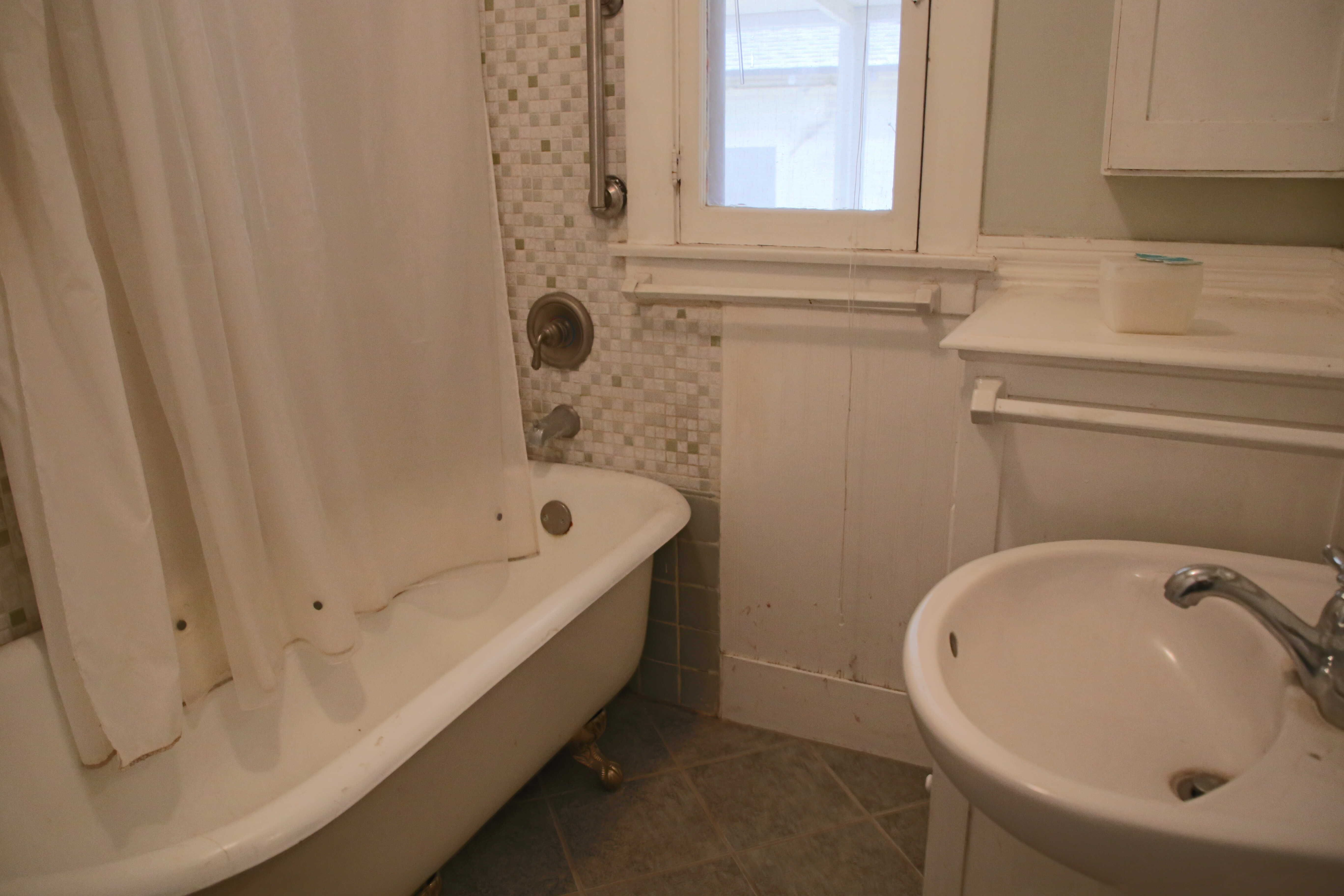 Bathroom with tile floor, pedestal sink, and 10-yr-old claw foot tub.