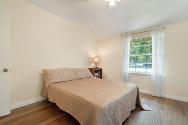 Spacious front bedroom with bamboo flooring and ceiling fan.