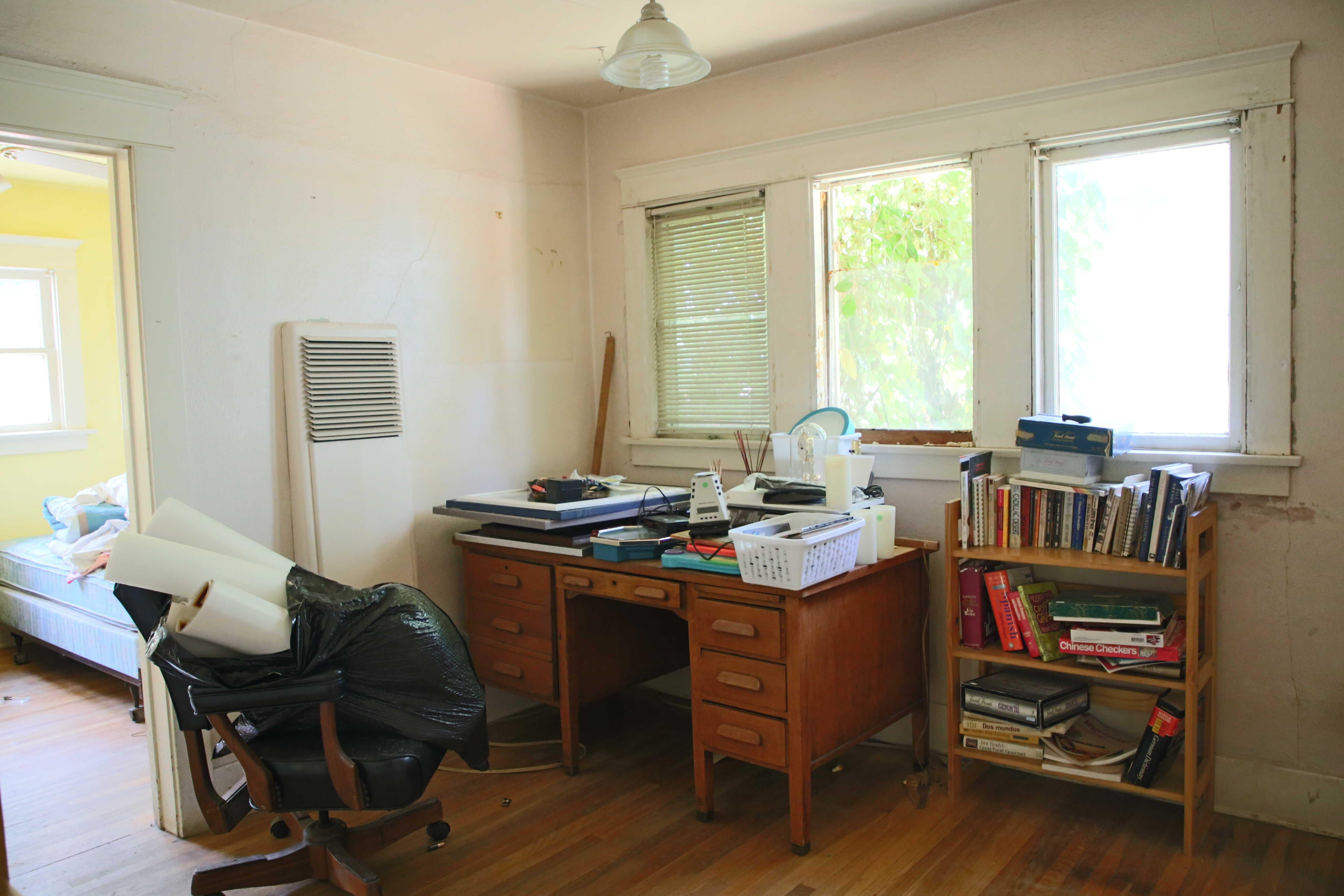 Middle bedroom with pocket windows and original hardwood floors.