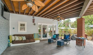 Huge covered patio with ceiling fans, and overlooking the pool and expansive backyard. Ideal space for watching TV and entertaining year-round.