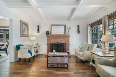 Gas and wood-burning fireplace with wood floors and coffered ceiling.