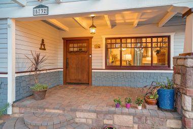 Elegant front porch with original wood front door.