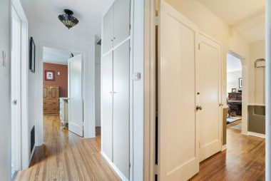 Hallway leading from back bedroom to front bedroom, with bathroom and laundry elevator in-between.