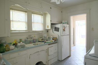 Kitchen with tile floor, and view into the laundry room.
