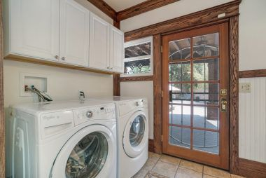 Laundry room with tile floor and convenient cabinetry.