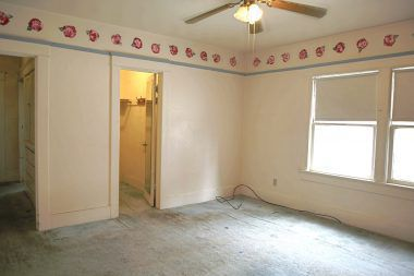 Huge middle bedroom with small walk-in closet and ceiling fan.