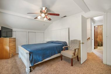 Second upstairs spacious bedroom with ample closet space, ceiling fan, and brand new carpet.