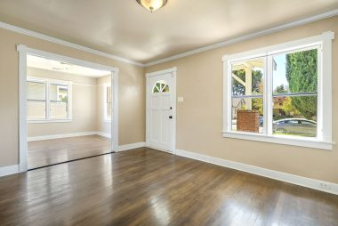 Front door entry. Hardwood floors throughout and view into the front bedroom (with a set of double doors in open position).