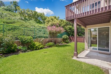 View of lovely landscaping and lush and private greenbelt behind the home.